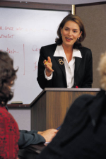 Photograph of a woman at a lectern, speaking to a group of people